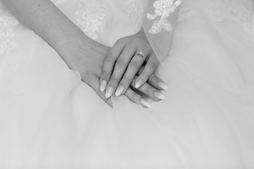 Photo of Bride's Hands on her dress with rings.jpg