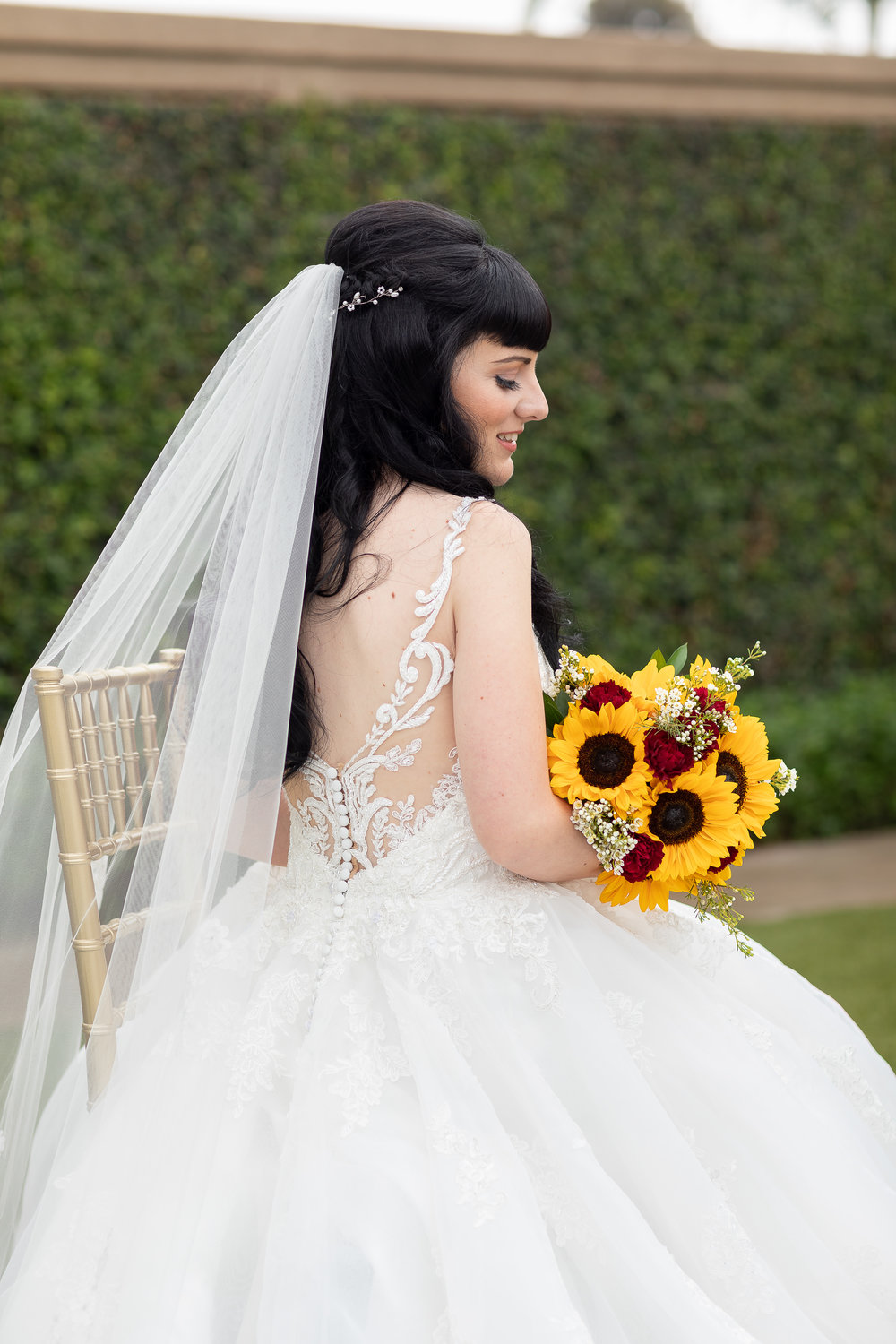 Photo of Gorgeous bride sitting in a chair in her wedding dress with a bouquet of sunflowers.jpg
