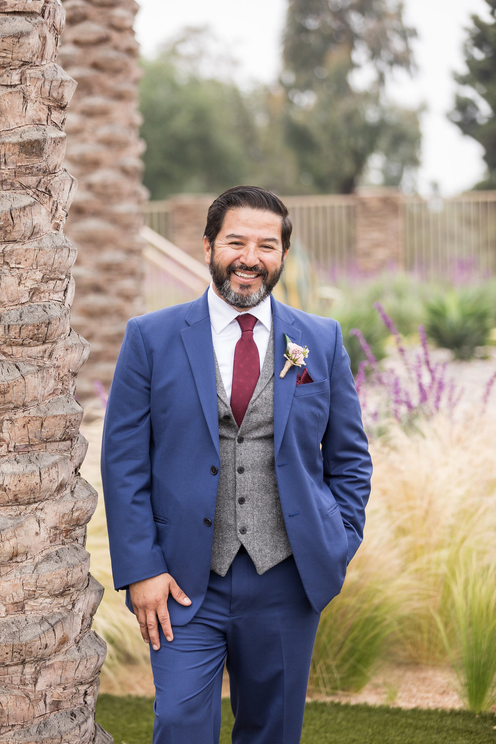 Photo of the handsome groom smiling next to a palm tree in his blue 2 piece wedding suit.jpg