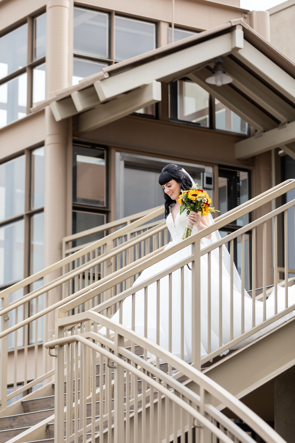 Photo of Bride walking down the stair with her sunflower bouquet and wedding dress.jpg
