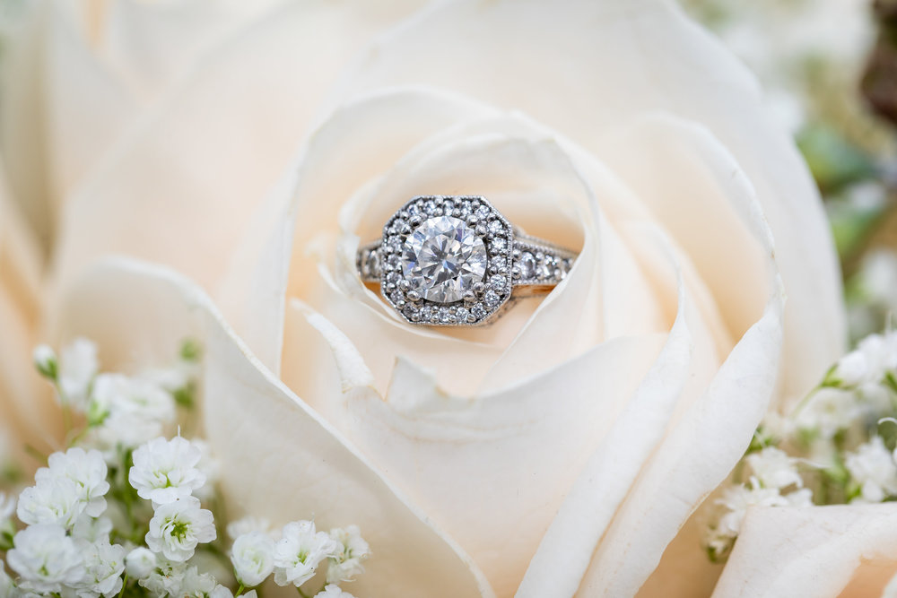 Photo of beautiful engagement ring laying within a white rose.jpg