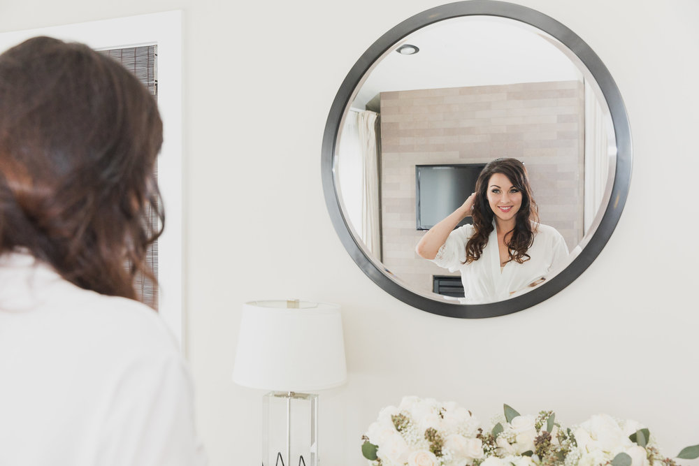 Photo of Happy Bride looking in mirror while getting ready.jpg