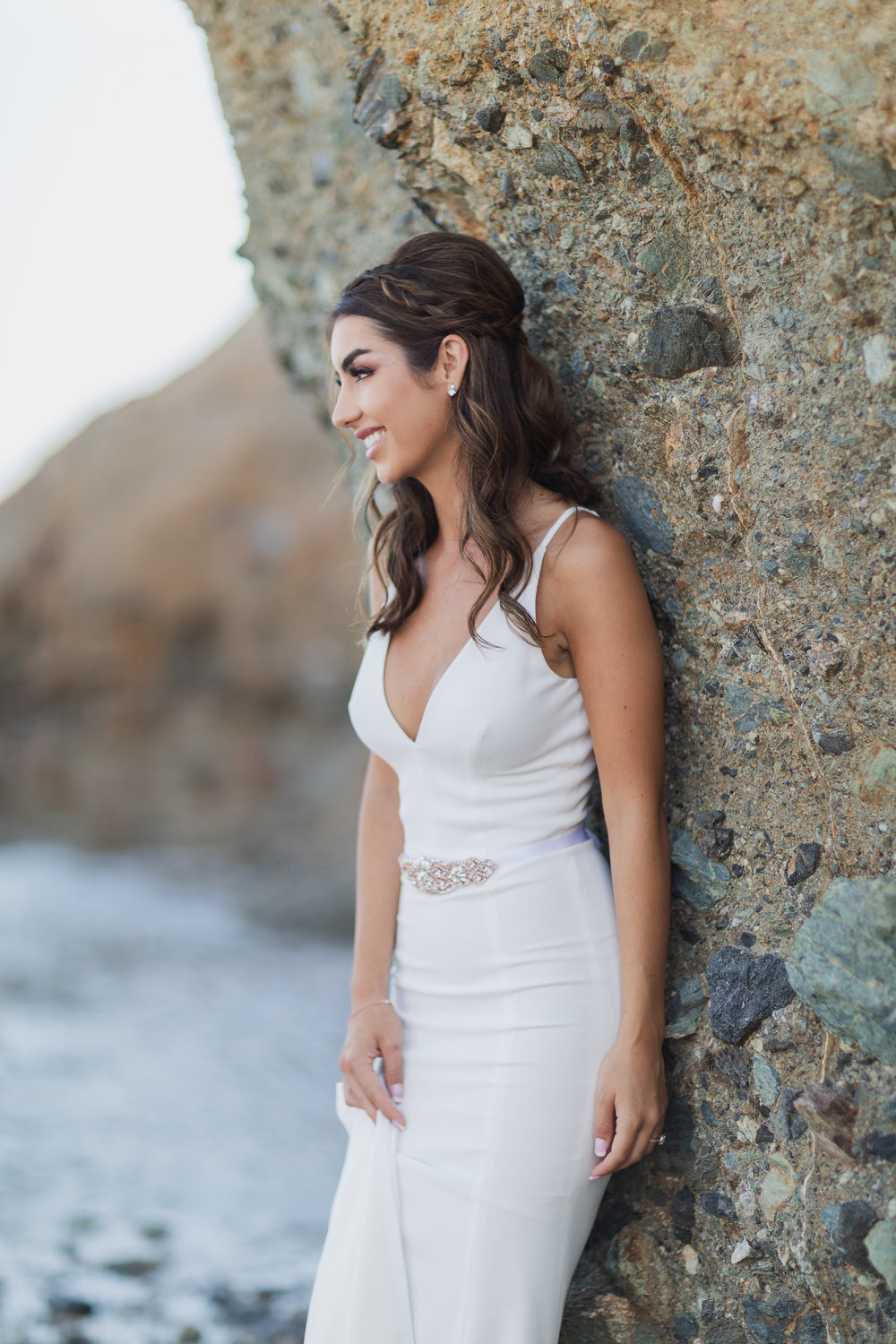 Photo of Beautiful Bride in a simple white wedding form fitting dress on the rocky beach.jpg