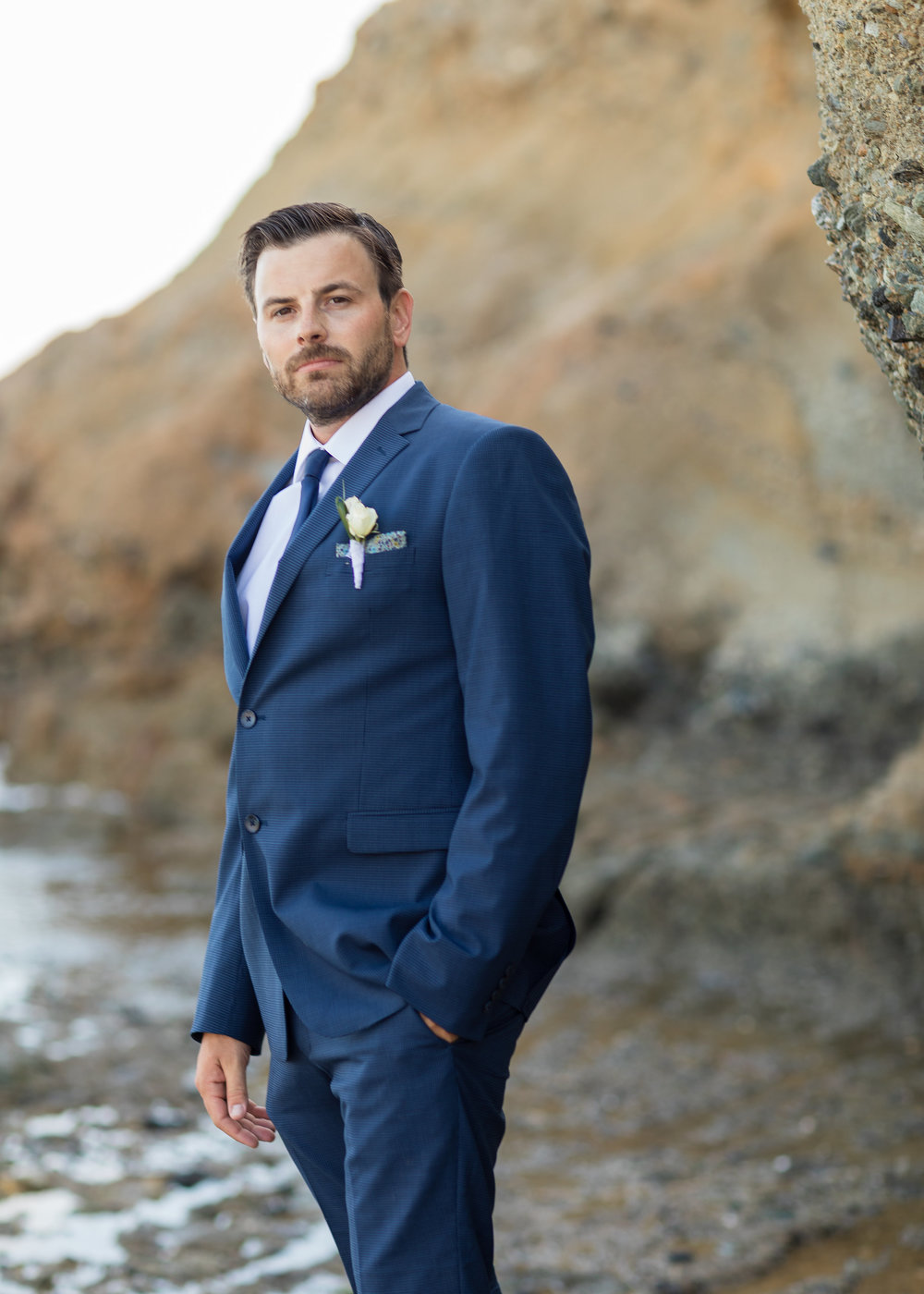 Photo of dashing Groom in a blue suit on the rocky shores of Treasure Island Laguna Beach.jpg