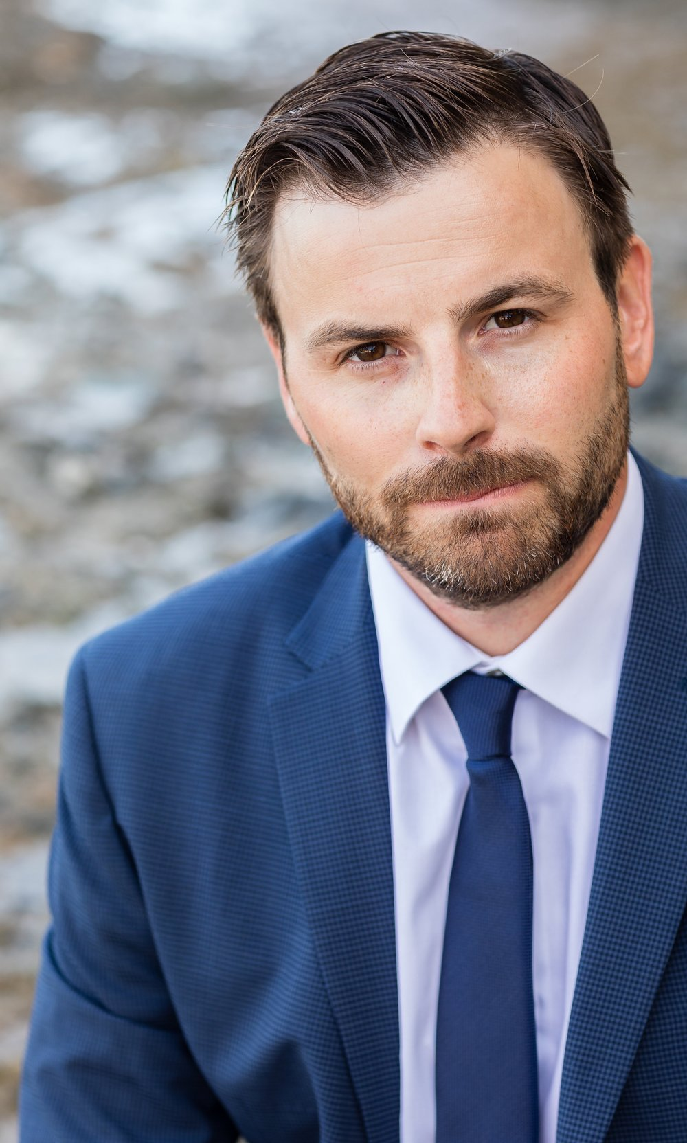 Photo of Handsome Wedding Groom in blue suit with facial hair on the rocky Laguna Beach shores.jpg