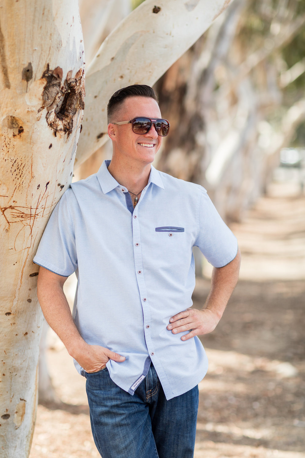 HB portrait of adult male standing by tree with sunglasses and a blue shirt.jpg