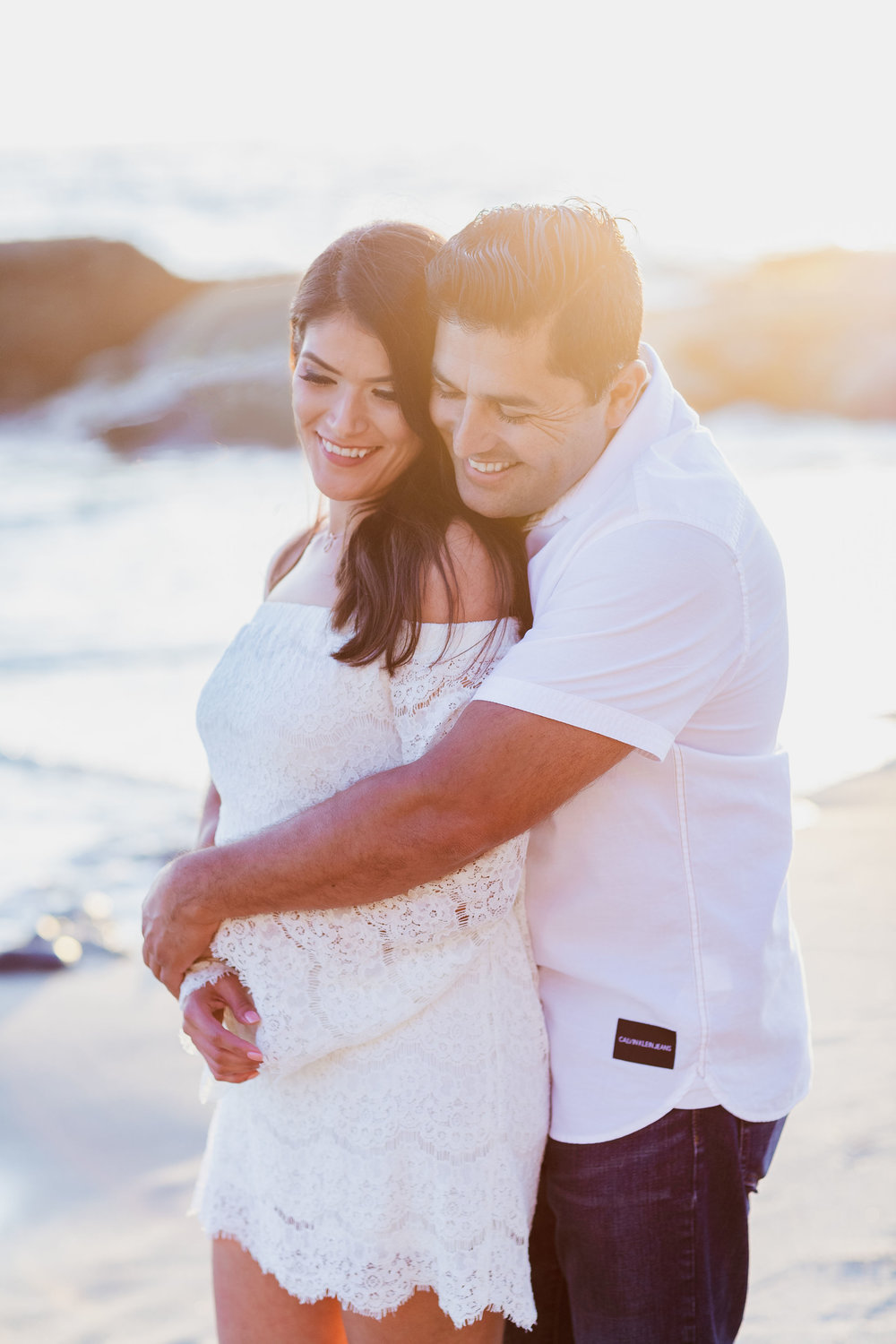 Romantic beach engagement photo with sunflare.jpg