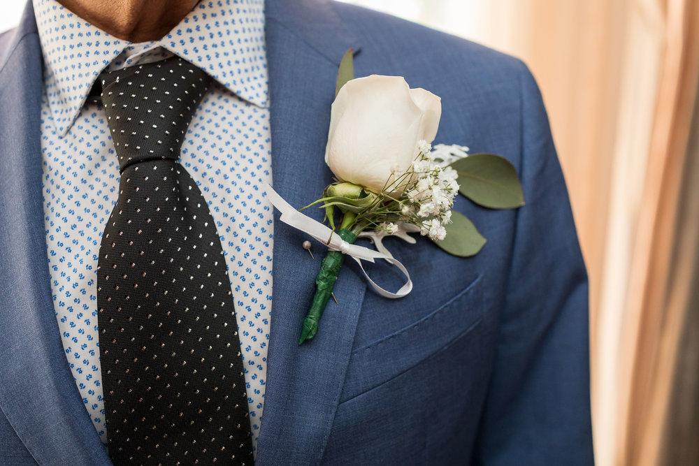 ! White rose boutenniere against a blue suit.jpg