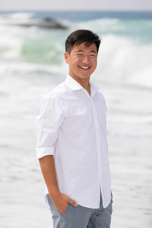 Male senior portrait in white shirt at beach.jpg