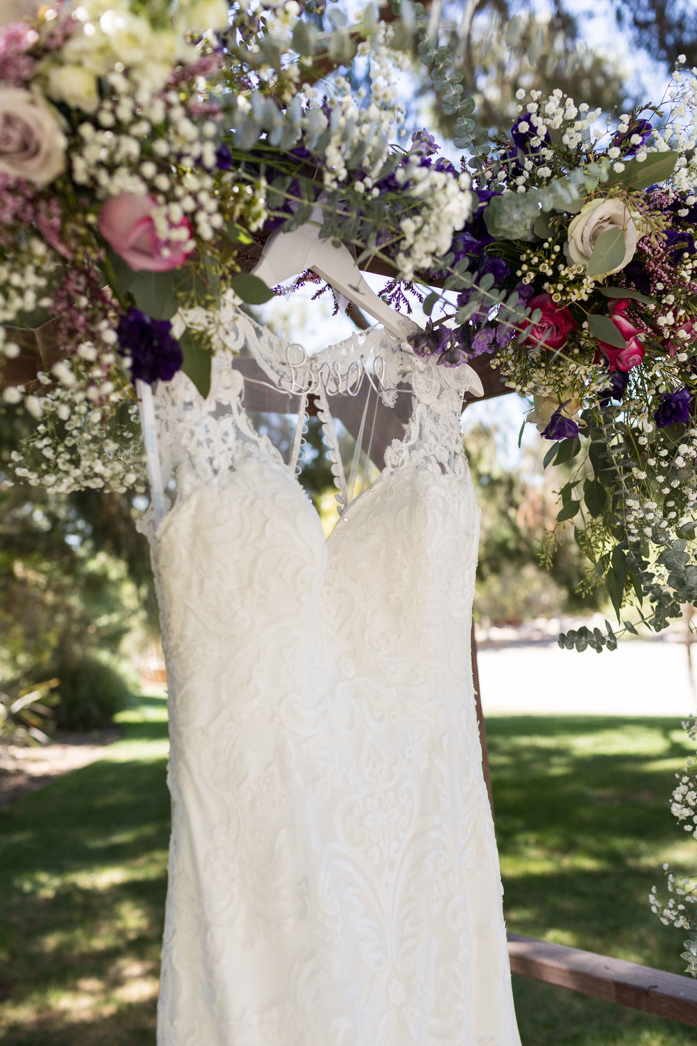 Wedding Dress Hanging Outdoor underneath Floral Arch.jpg