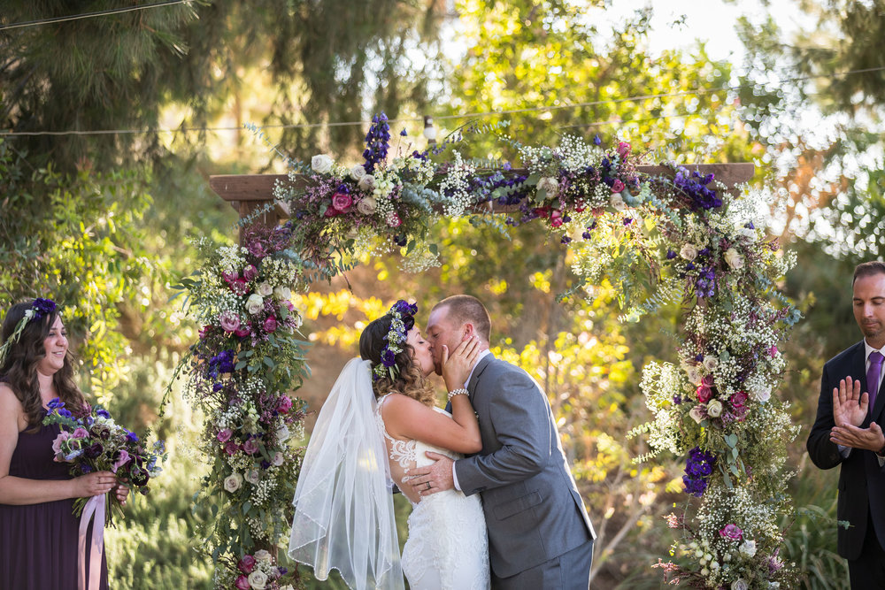 ! Wedding Kiss underneath a floral arch at Blomgren Ranch.jpg