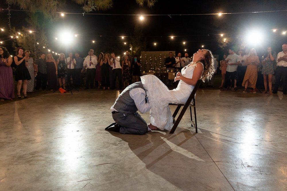 Groom Getting Garter from Bride at Reception.jpg
