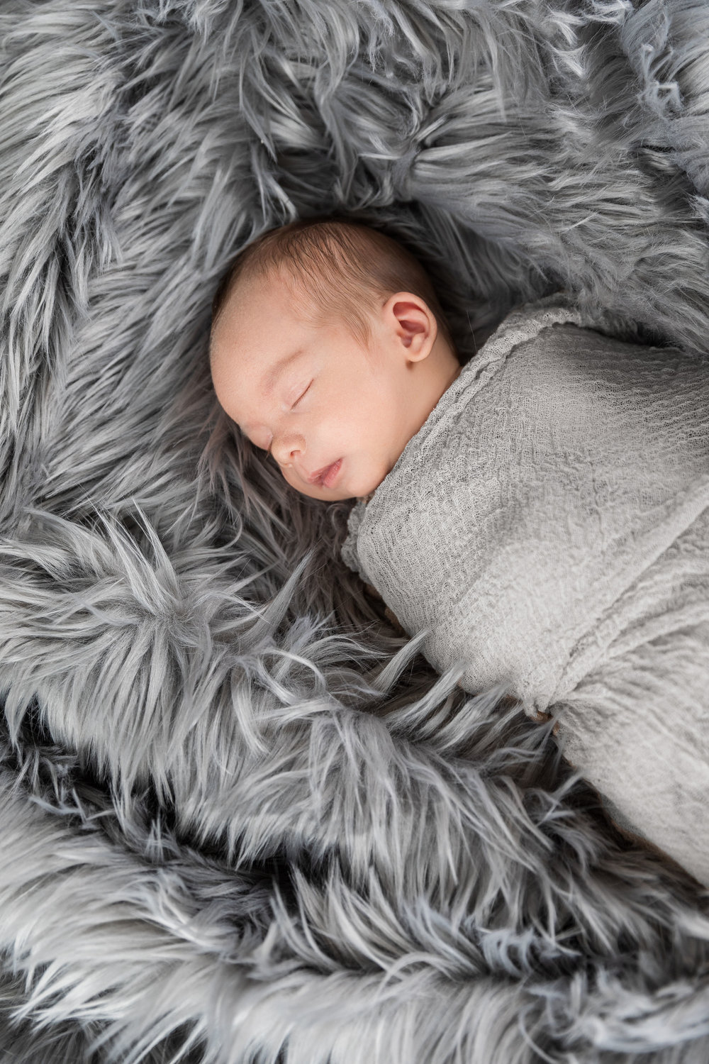 1 month old boy sleeping in a gray wrap on gray fur james korin portrait photography home session.jpg