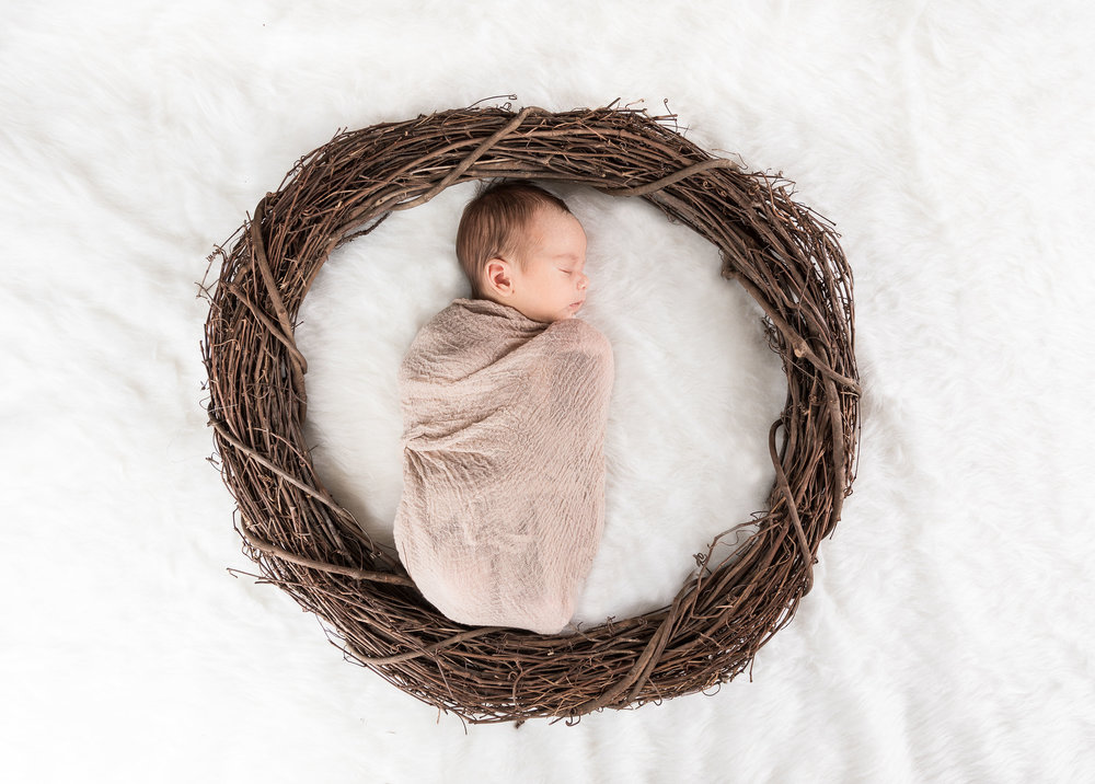 Little angel sleeping in a wreath with a white fur background james korin photography.jpg