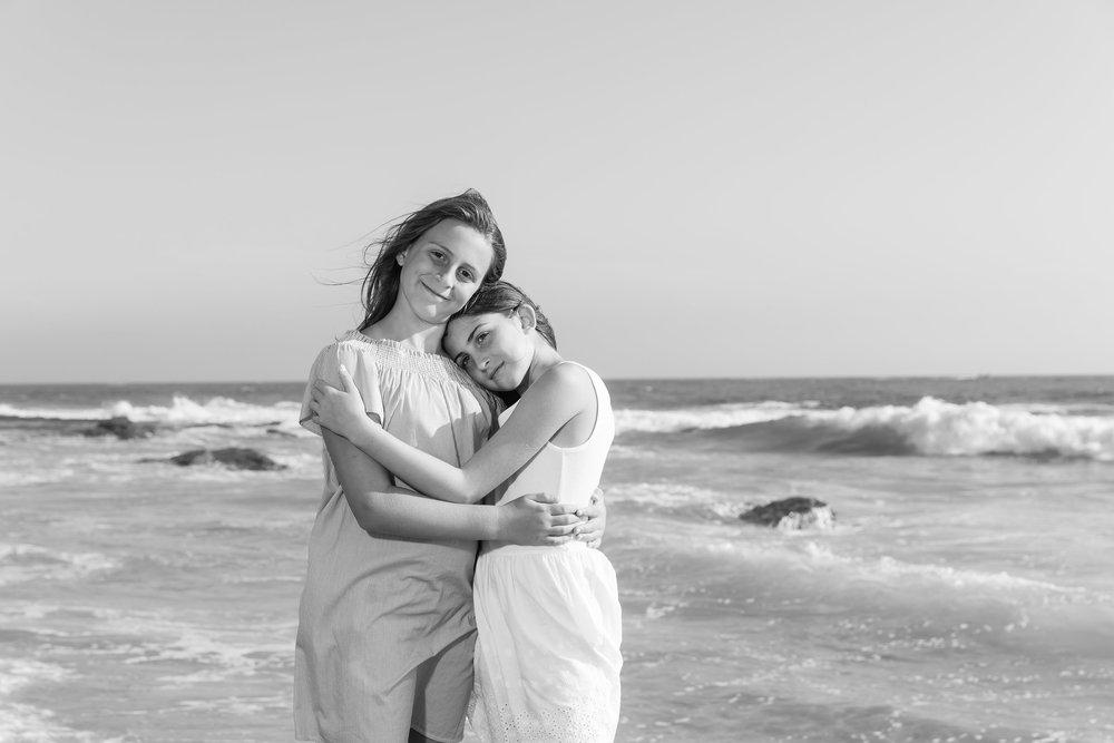 kid siblings hugging on the beach in newport crystal cove.jpg