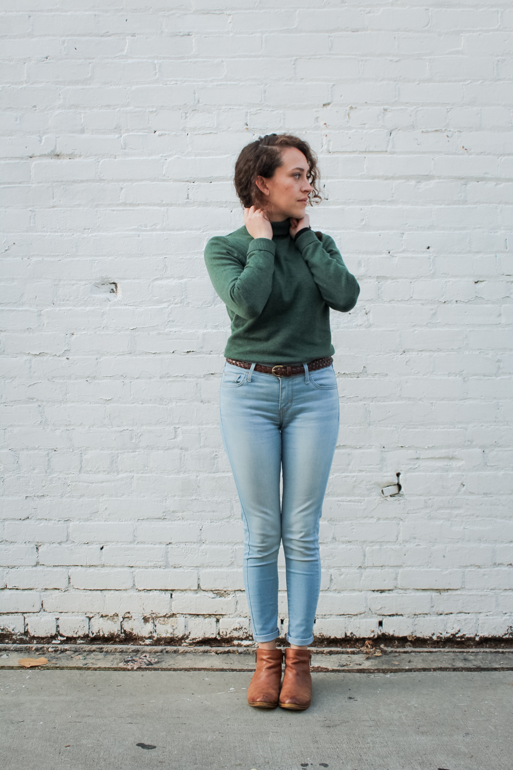 Spring 10x10/Unfancy Remix capsule wardrobe outfit. Light wash levis skinny jeans with ankle boots and a fitted turtleneck sweater | tinted green