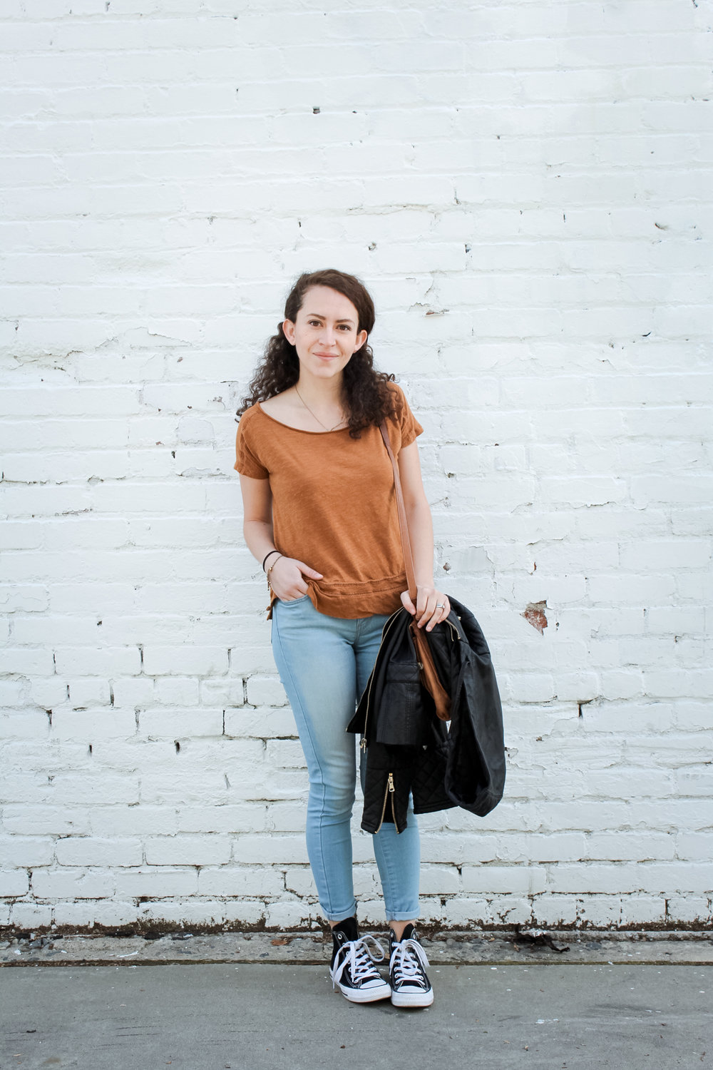 my outfit for day 9 of the unfancy remix/spring 10x10 capsule wardrobe challenge was my thrifted copper t shirt with light wash skinny jeans and high top converse. i added my black faux leather jacket and fossil crossbody bag to the look | tintedgreen