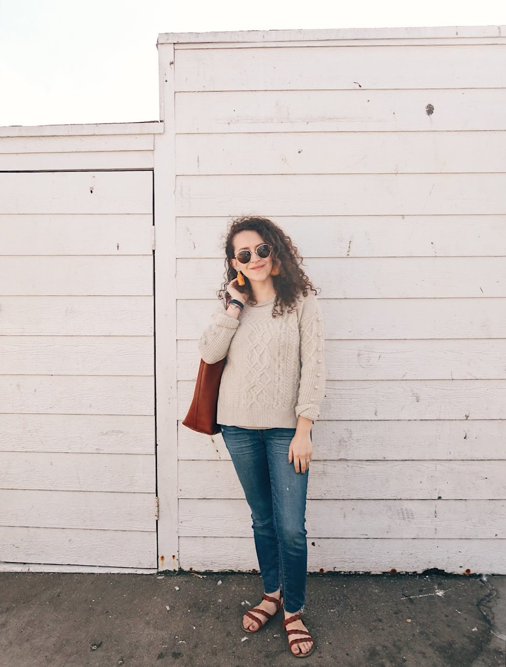 a winter beach outfit -- neutral sweater, midwash jeans, braided sandals and tassel earrings