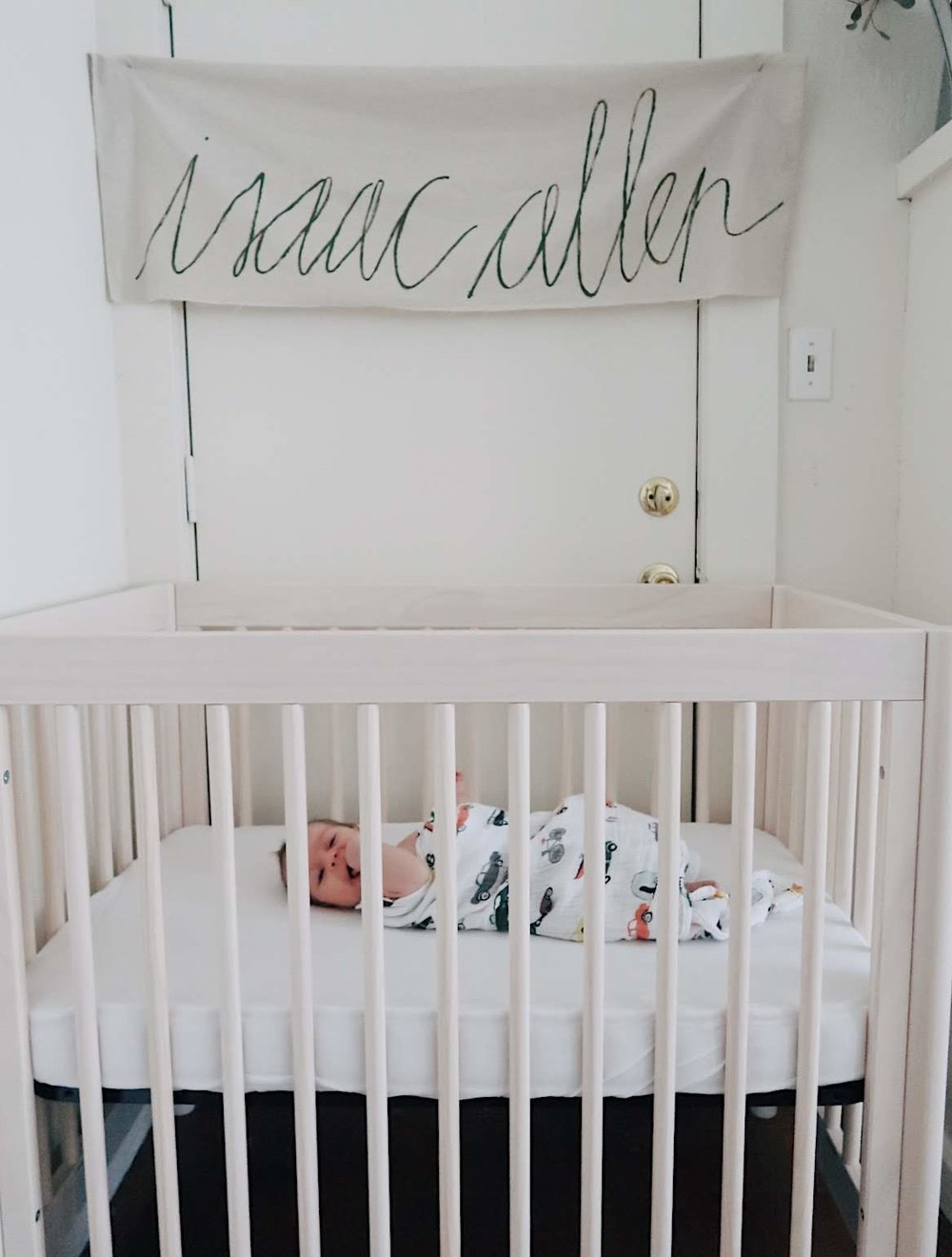 simple gender neutral nursery nook in a small apartment with a mini crib by babyletto