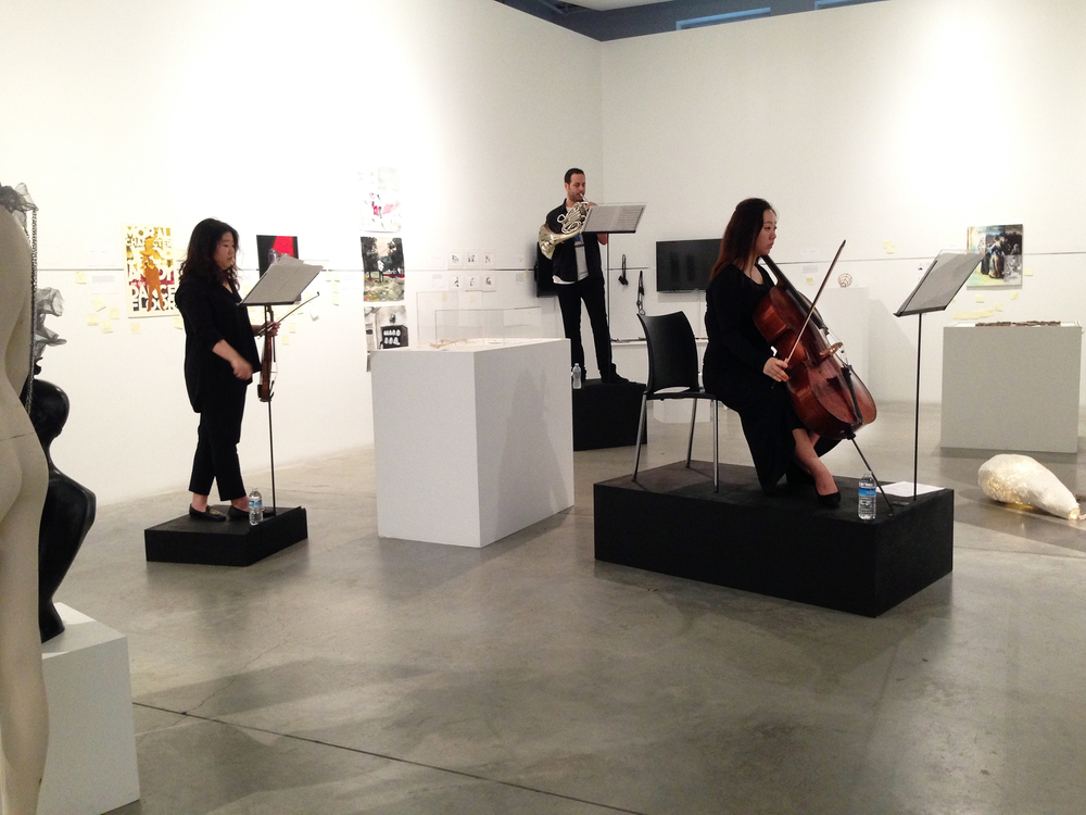 The partial view of the orchestra arrangement in the left wing of the gallery space. Each musician is standing on a black pedestal with fixed metal stand. The stands and pedestals vary in size.