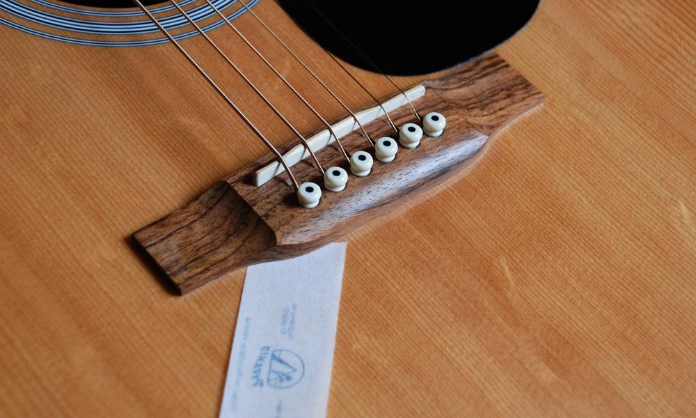 Kaum sichtbarer, jedoch erheblicher Schaden: die Bridge dieser Western-Gitarre hat sich leicht von der Decke abgelöst. Papiertest: nicht bestanden!