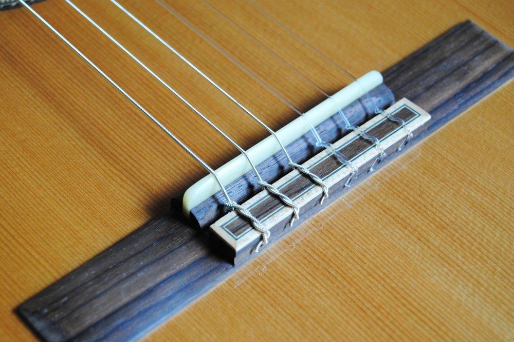 Der Steg einer Konzert-Gitarre: die Saiten werden mit einem speziellen Knoten daran befestigt.