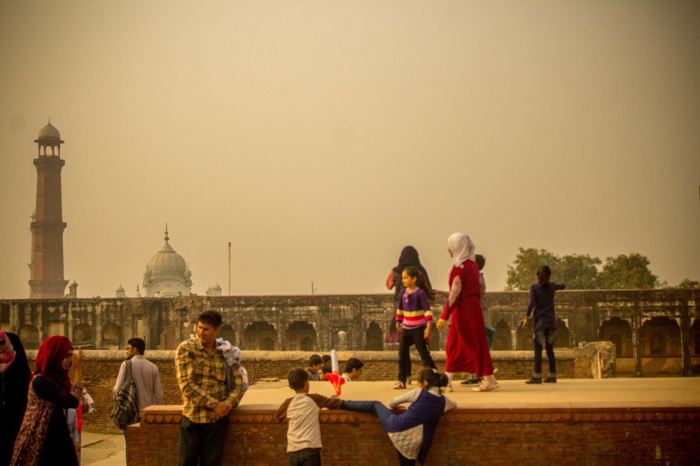 Kiddos climb onto a wall in Lahore fort during an afternoon family outing.