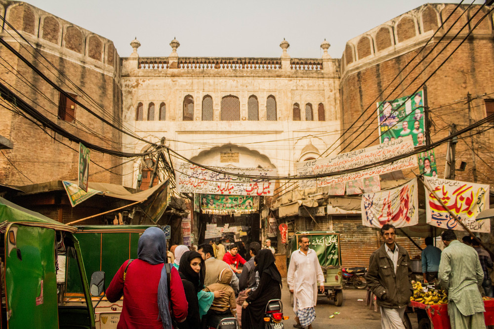 Our Director of Photography, Jen (red and blue), follows a friend of ours into Old Lahore via Lahori gate, one of 13 original gates.