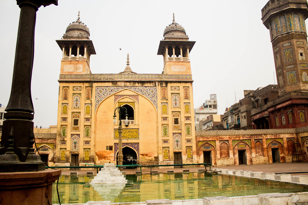 The  faience  tile work of the Wazir Khan Masjid reflects in the mosque courtyard's fountain pool.