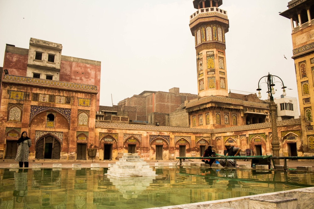Visitors pause alongside the reflecting pool of the Wazir Khan Masjid, surrounded by the mosque's famous  faience  tile work.