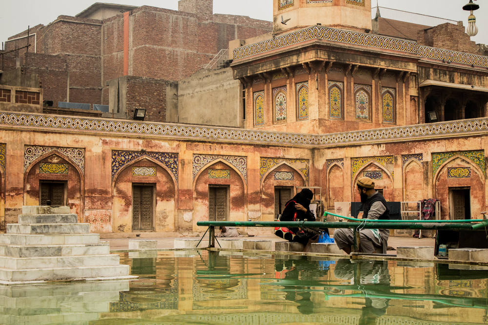 A Lahori couple pause and rest next to the Wazir Khan Masjid's reflecting pool just before sunset in Old Lahore.