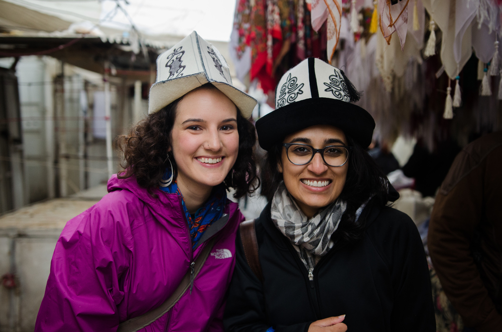 Olivia (left) and Lena (right) trying on hats in Osh, Kyrgyzstan. Photo taken by Jennifer Ciochon, GIRLWITHABOOK Board Member