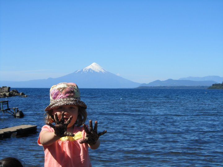 Daughter #1, showing her hands, black with volcanic sand and the Osorno Volcano in Chile. February 2011.