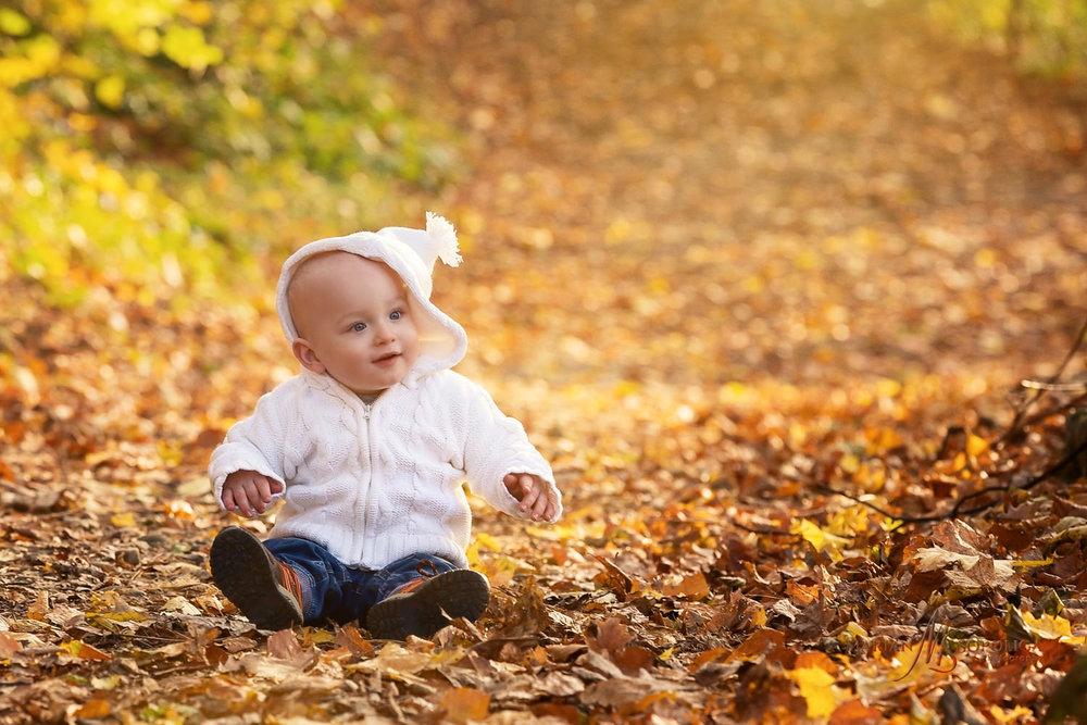 Podzimní dětský portrét klučíka, sedícího v zabarveném listí na Petříně v Praze.