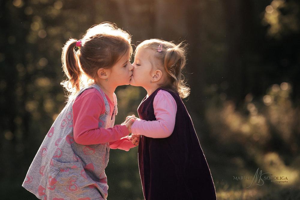 Rodinný portrét dvou sestřiček, které se pusinkují. Fotografie byla pořízená v brněnském parku.