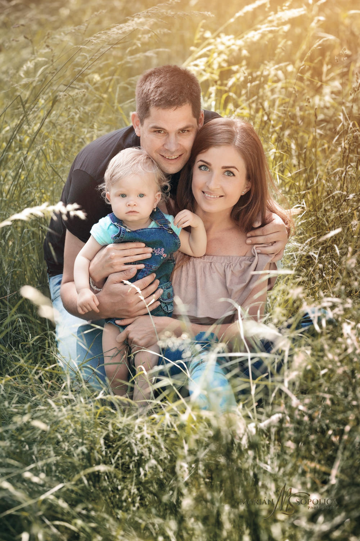 Portrét mladé rodinky s malou dcerkou na louce v botanické zahradě v Praze.
