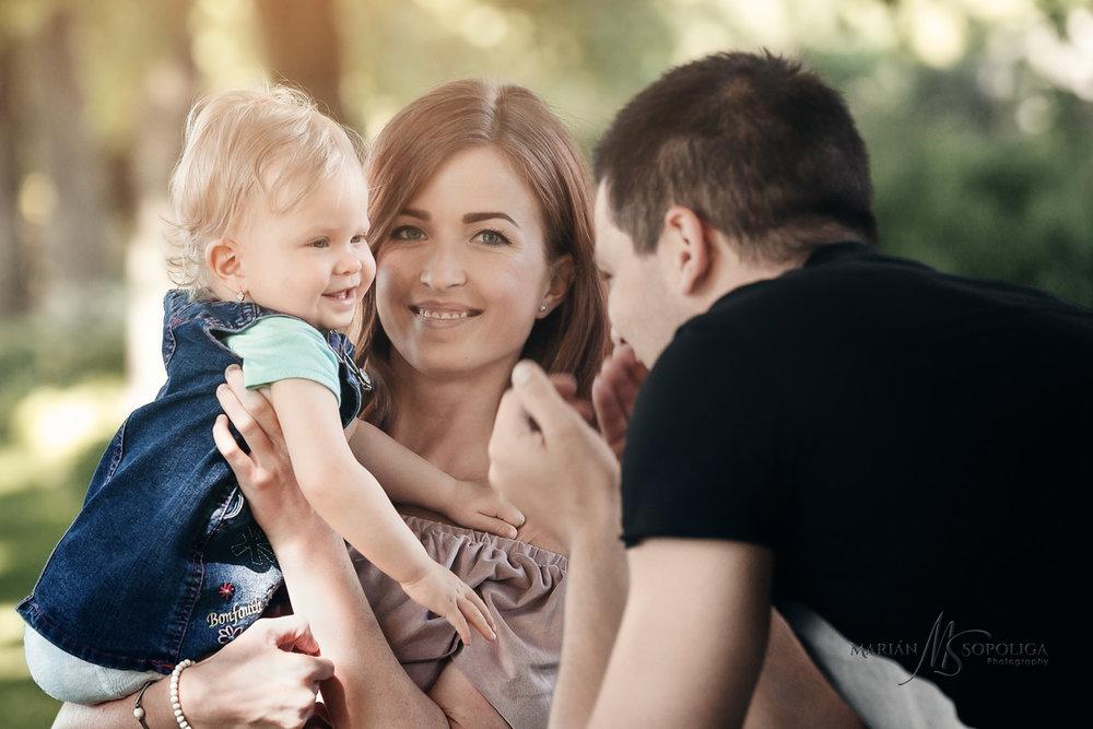 Rodinné foto rodičů s malou dcerkou v botanické zahradě v Praze. Tatínek upoutává pozornost dcerky hrou.