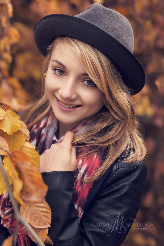 Podzimní portrétní focení teenagerů v Praze na Petříně. Slečna v klouboučku se šálou v podzimním zabarveném listí.