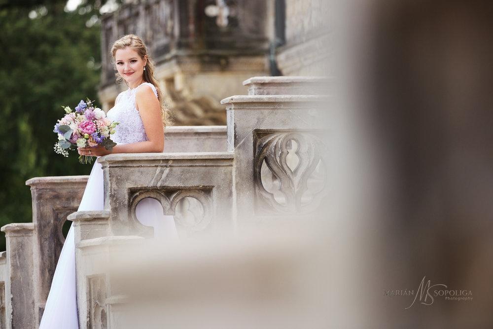 nevesta-se-svatebni-kytici-na-schodisti-na-zamku-sychrov.jpg
