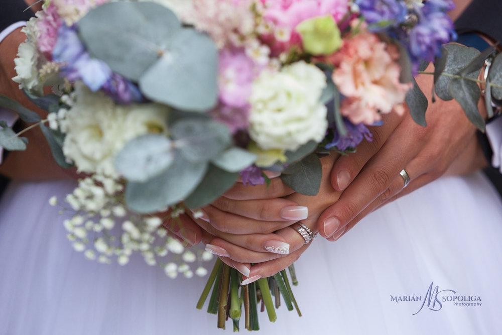 detail-svatebni-kytice-a-ruce-novomanzelu-se-zasnubnimi-prstynky