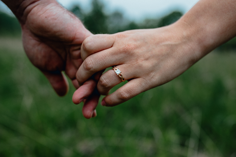 bride-and-groom-holding-hands-engagement-ring-in-field.jpg