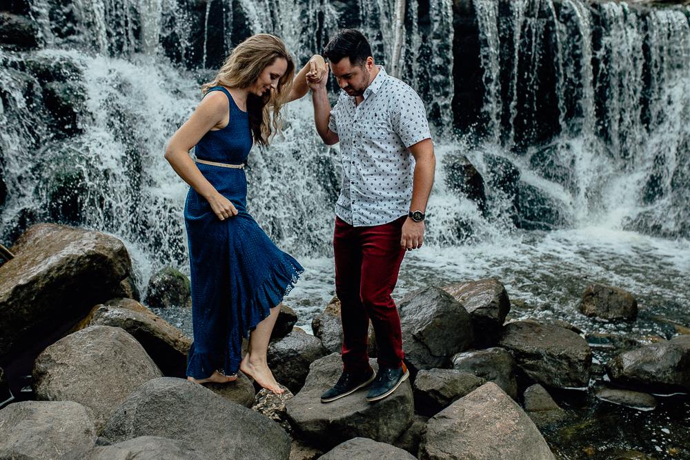 engaged-bride-and-groom-walk-by-waterfall.jpg