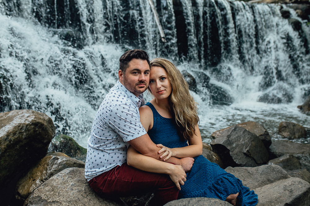 engaged-bride-and-groom-sitting-by-waterfall.jpg