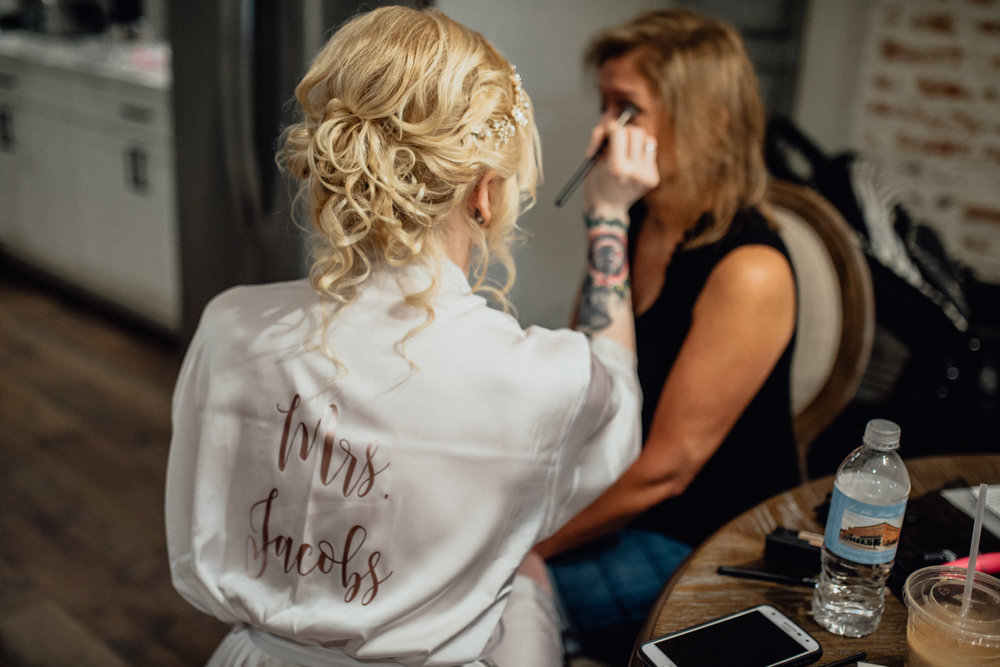 Bride applying makeup to mother