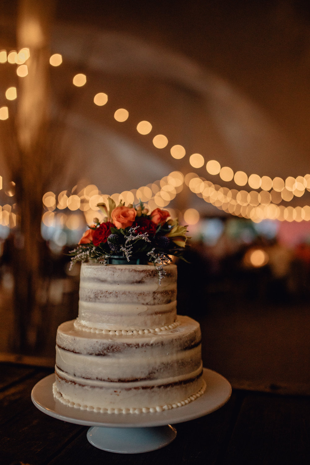 cake with string lights at reception at oak hill weddings