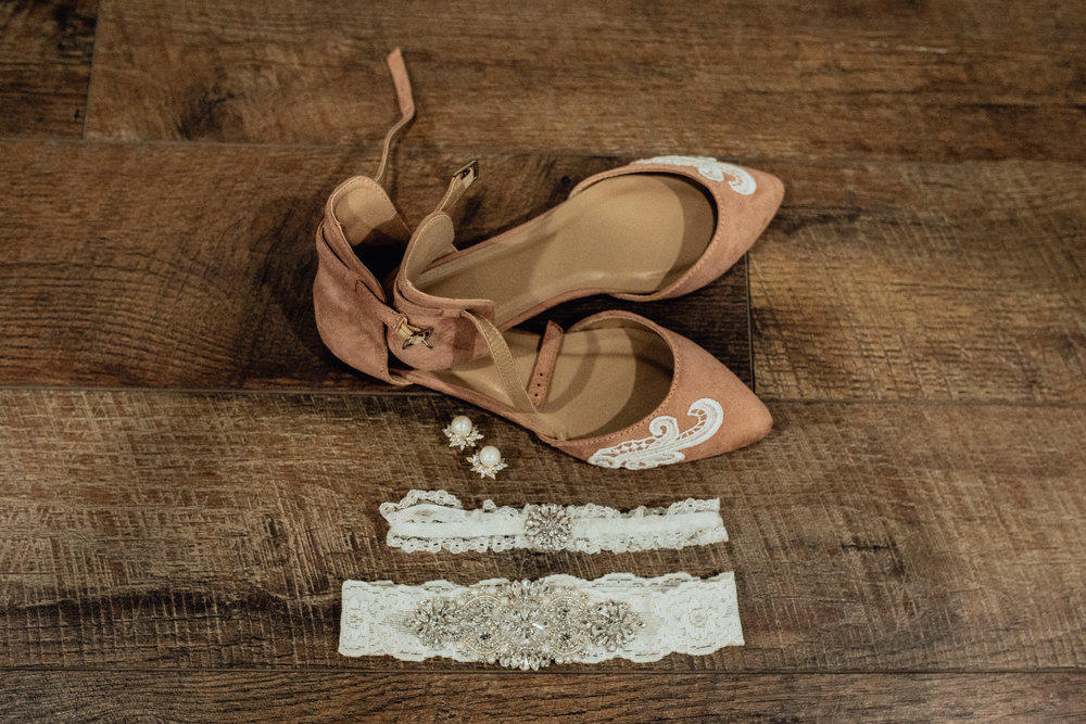Bridal details shoes and garter closeup on wood