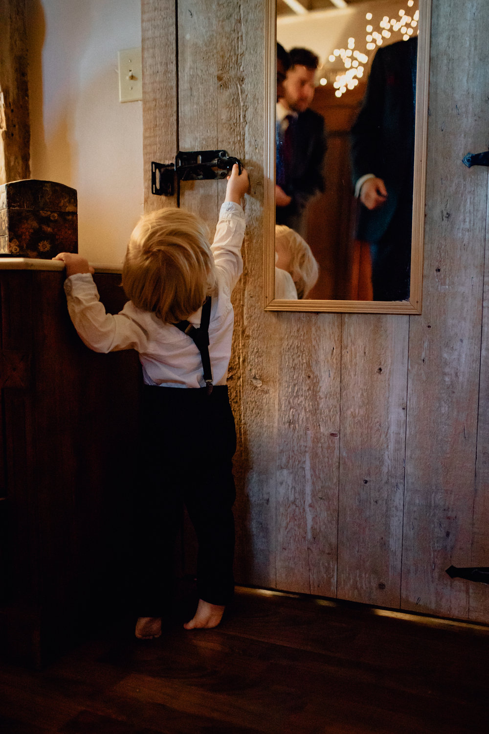 Toddler reaching for door handle in suit