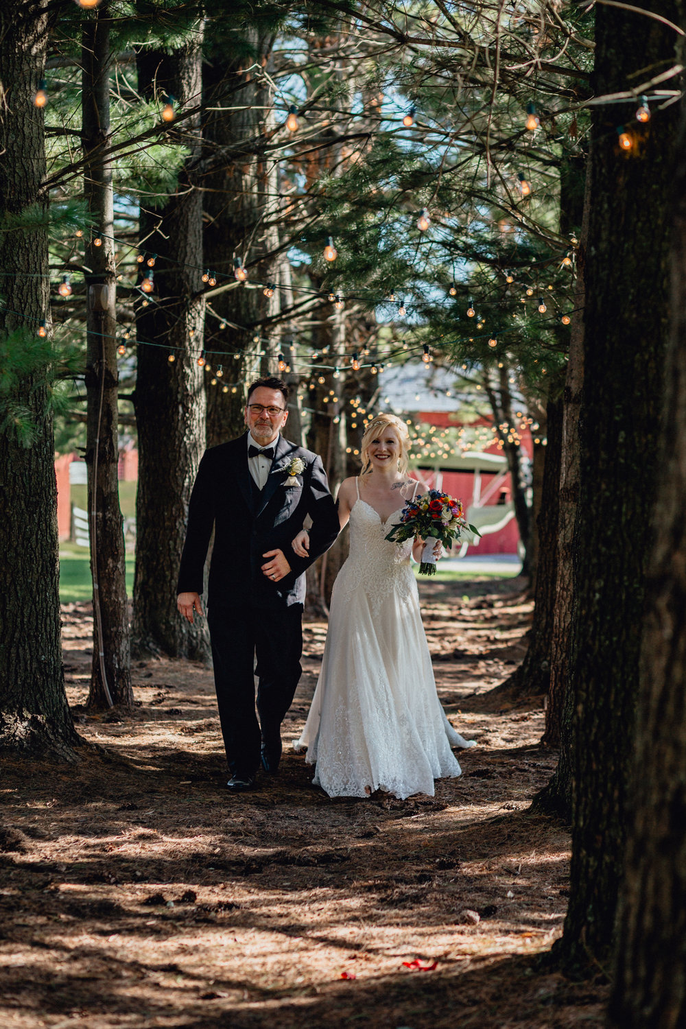 Bride walking down path of pines with father to ceremony at oak hill weddings
