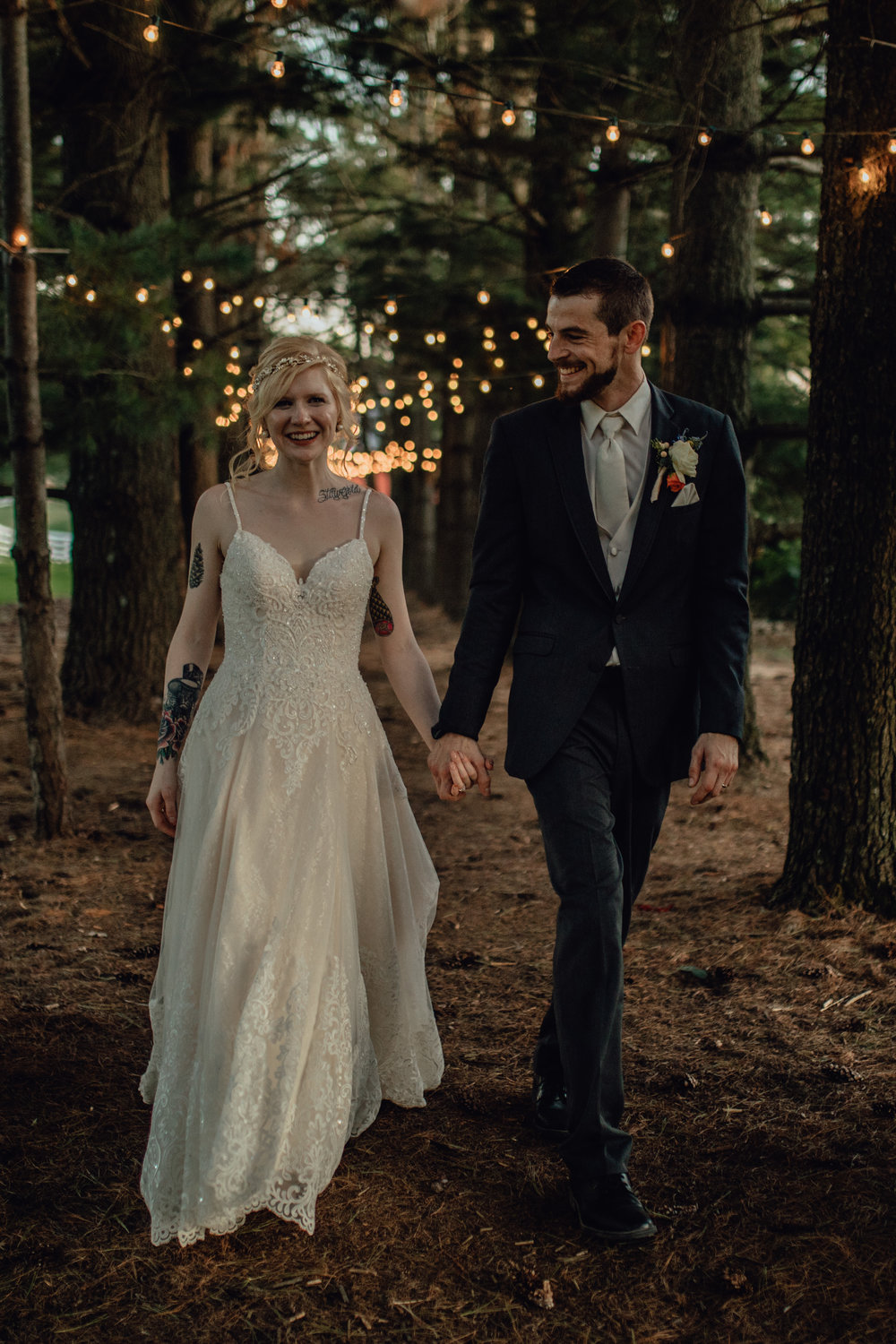 bride and groom portrait under string lights in forest at oak hill weddings path of pines