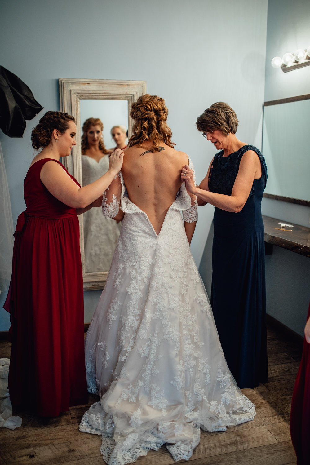 mother-and-bridesmaid-helping-bride-into-dress.jpg